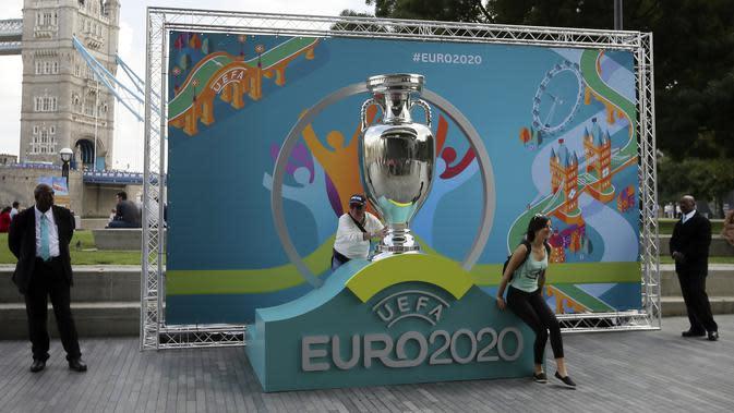 Warga berpose dengan logo Piala Eropa 2020 saat peluncuran di London, Inggris, 21 September 2016. UEFA memundurkan jadwal Piala Eropa 2020 hingga tahun 2021. (AP Photo/Tim Ireland, File)