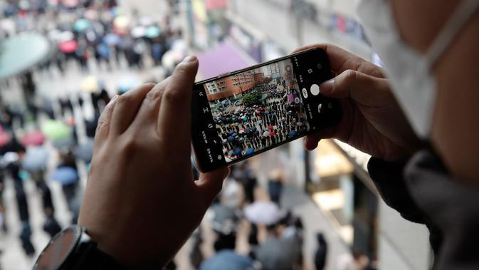 Seorang pria mengambil foto orang-orang yang berbaris untuk membeli masker pelindung di luar sebuah department store di Seoul, Jumat (28/2/2020). Penyebaran virus corona di Korea Selatan sendiri merupakan salah satu yang terbesar di luar China Daratan. (AP /Lee Jin-man)