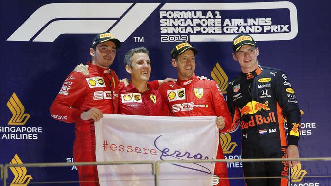 Pembalap Ferrari Sebastian Vettel bersama Charles Leclerc dan Max Verstappen dari Red Bull berpose di podium setelah memenangkan balapan Formula Satu (F1) Grand Prix Singapura di Sirkuit Jalan Marina Bay, Singapura (22/9/2019). (AP Photo/Vincent Thian)