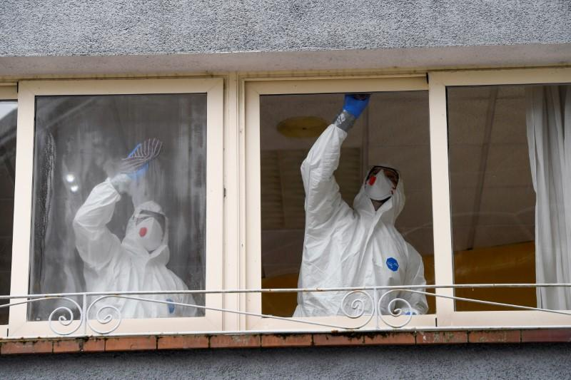 FILE PHOTO: Sanitary workers clean the nursing home where a woman died and several residents and care providers have been diagnosed with coronavirus disease (COVID-19) in Grado