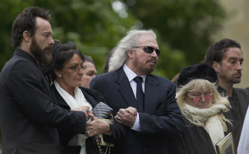 Barry Gibb, center, and Robin Gibb's wife Dwina Gibb, right, who holds an order of service, react at the graveside during the burial of Robin Gibb outside St Mary's Church in Thame, England, Friday, June 8, 2012. Robin Gibb a member of the iconic Bee Gees pop group died May 20, after a long battle with cancer.(AP Photo/Alastair Grant)
