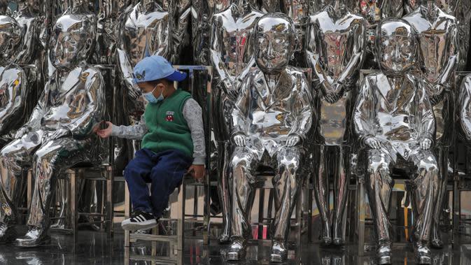 Seorang anak yang mengenakan masker untuk mengekang penyebaran COVID-19 memegang patung di Beijing, China, Minggu (11/10/2020). Meski penyebaran COVID-19 hampir diberantas di China, pandemi masih melonjak di seluruh dunia dengan jumlah kematian yang terus meningkat. (AP Photo/Andy Wong)