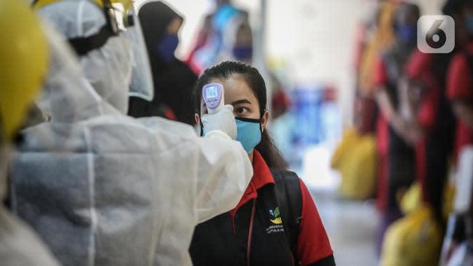 SeorangTKI Ilegal yang dipulangkan dari Malaysia diukur suhu tubuhnya setibanya di Pelabuhan Tanjung Priok, Jakarta, Jumat (12/6/2020). Sebanyak 436 TKI Ilegal tersebut nantinya akan dipulangkan ke daerah asalnya di 22 provinsi. (Liputan6.com/Faizal Fanani)