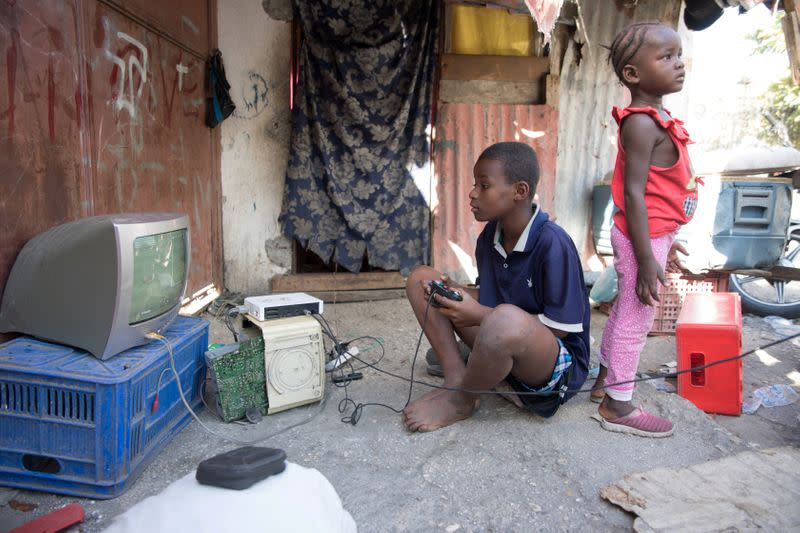 Boy plays video games on the street, outside of Notre Dame de l'Assomption Cathedral (Our Lady of the Assumption), in Port-au-Prince