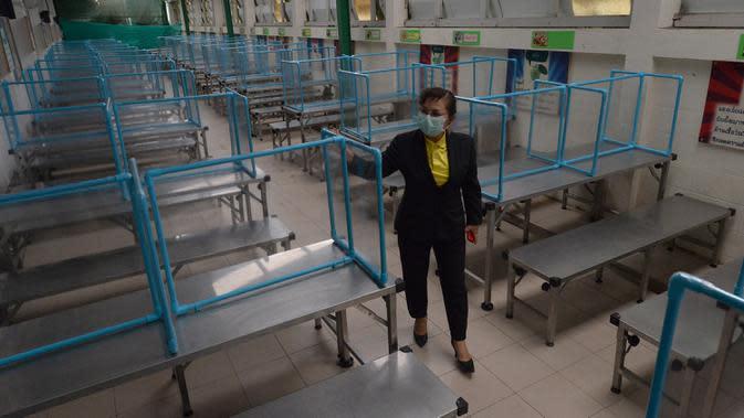 Seorang guru memeriksa lembaran plastik yang digunakan untuk membantu mencegah penyebaran COVID-19 di sebuah sekolah di Bangkok, Thailand, Selasa (23/6/2020). Sejumlah sekolah di Thailand dijadwalkan akan dibuka kembali pada 1 Juli mendatang. (Xinhua/Rachen Sageamsak)