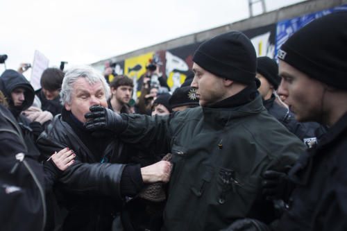 German police struggles with a protestor as they protect a part of the former Berlin Wall in Berlin, Germany, Friday, March 1, 2013. Berliners are protesting as a construction company removes a section of a historic stretch of the Berlin Wall known as the East Side Gallery to provide access to a riverside plot where luxury condominiums are being built. Since German reunification, the stretch of the wall has been preserved as a historical monument and transformed into an open air gallery painted with colorful murals, and has become a popular tourist attraction. (AP Photo/Markus Schreiber)
