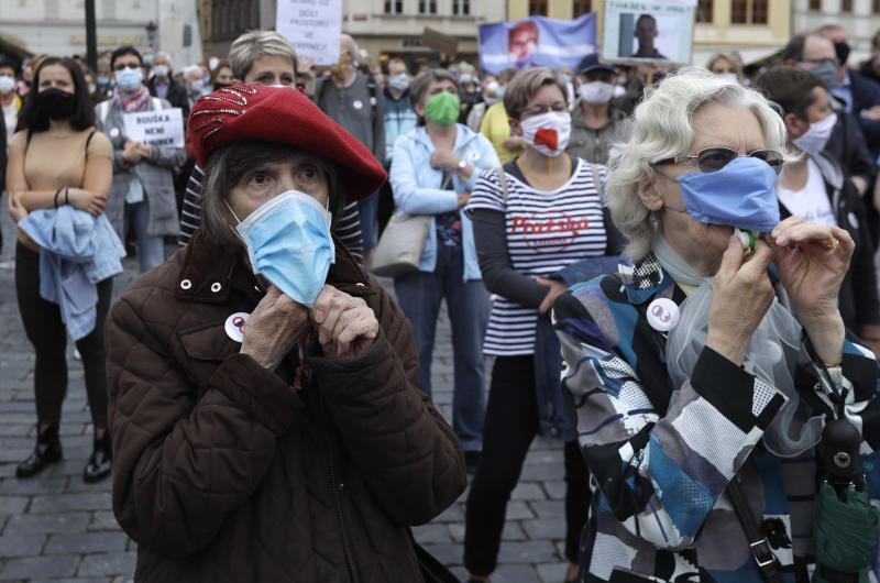 Elderly women wearing face masks to protect against coronavirus, blow whistles, during a protest at the Old Town Square in Prague, Czech Republic, Tuesday, June 9, 2020. Hundreds of people protested in the Czech capital to draw attention to the government's insufficient and chaotic response to the coronavirus outbreak and other financial issues. (AP Photo/Petr David Josek)