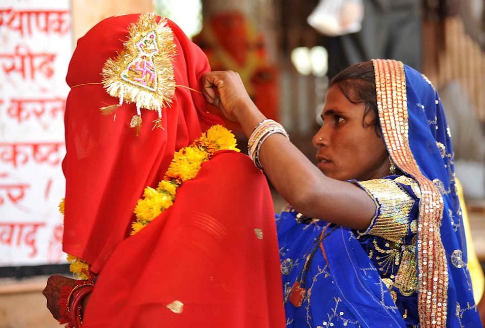 A woman adjusts the veil of her 15-year-old child bride daughter Sintu at the Balaji temple in Kamkheda village, in the western Indian state of Rajasthan, Saturday, May 7, 2011. Ignoring laws that ban child marriages, young children are still married off as part of centuries-old custom in some Indian villages. India law prohibits marriage for women younger than 18 and men under age 21. (AP Photo/Prakash Hatvalne)