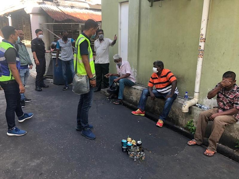 Four Malaysians and one Indian national were gathered together holding cans of alcohol at the narrow side lane off Burma Road when authorities chanced upon them. — Picture courtesy of Royal Malaysia Police