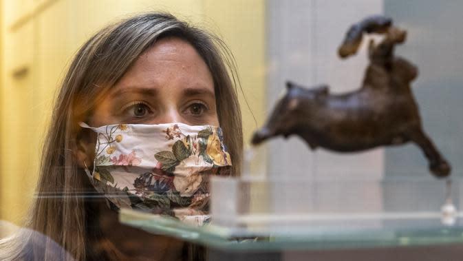 Seorang staf mengamati sebuah benda pameran saat pratinjau media menjelang pembukaan kembali Museum Inggris di London, Inggris (25/8/2020). Museum tersebut akan dibuka kembali pada 27 Agustus. (Xinhua/Han Yan)