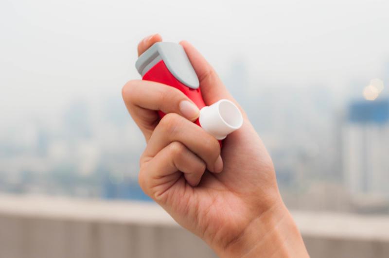 Une jeune femme utilise un inhalateur pour l'asthme à l'extérieur