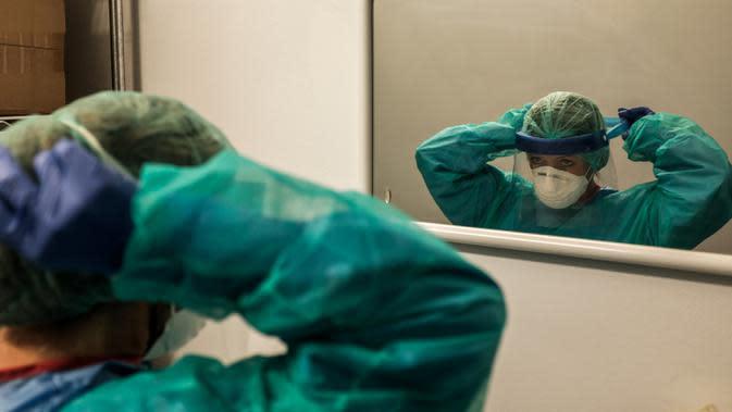 Seorang perawat mengenakan peralatan kerjanya untuk memulai shift di rumah sakit Cremona, tenggara Milan, Lombardy, 12 Maret 2020. Para pekerja kesehatan Italia kelelahan setelah selama bermingu-minggu mereka yang berada di garda terdepan memerangi pandemi virus corona. (Paolo MIRANDA/AFP)