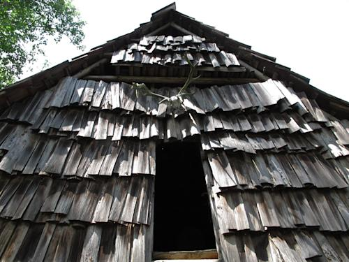 Hand-hewn shingles cover the facade of a log barn at Turtle Island Preserve in Triplett, N.C., on Thursday, June 27, 2013. (AP Photo/Allen Breed)