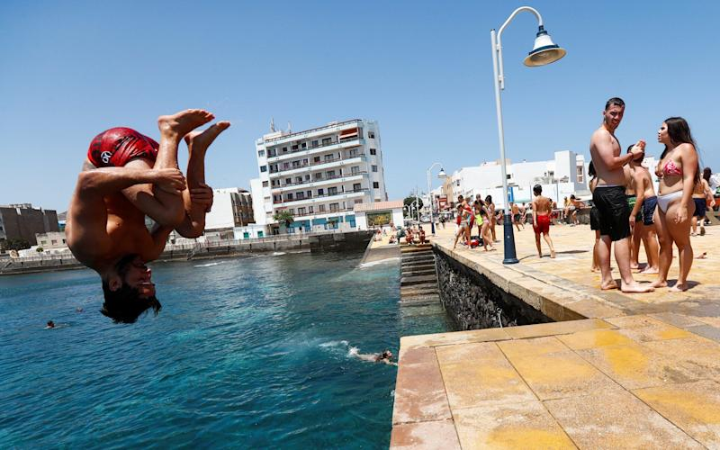 A young man jumps to bathe on Arinaga Beach as some Spanish provinces are allowed to ease lockdown restrictions during phase two, on the island of Gran Canaria - BORJA SUAREZ/ REUTERS