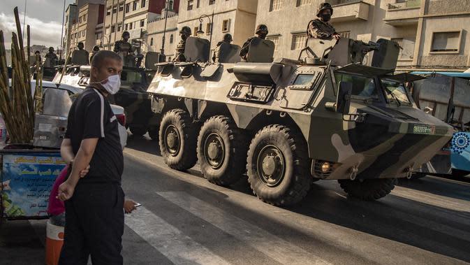 Tentara Maroko berpatroli di tengah wabah baru virus corona baru di kota Tangiers (11/8/2020). Tentara dikerahkan untuk meredam Lonjakan kasus Covid-19 di negara tersebut. (AFP/Fadel Senna)