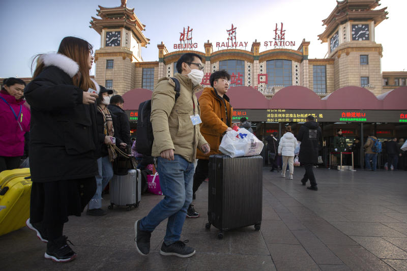 A traveler wears a face mask as he walks outside of the Beijing Railway Station in Beijing, Monday, Jan. 20, 2020. China reported Monday a sharp rise in the number of people infected with a new coronavirus, including the first cases in the capital. The outbreak coincides with the country's busiest travel period, as millions board trains and planes for the Lunar New Year holidays. (AP Photo/Mark Schiefelbein)