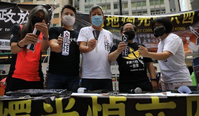 Leung Kwok-hung, Andrew Wan Siu-kin, Lee Cheuk-yan, Albert Ho Chun-yan and Chow Hang-tung of the Hong Kong Alliance in Support of Patriotic Democratic Movements of China distribute candles at a street booth in Causeway Bay on May 31. Photo: May Tse