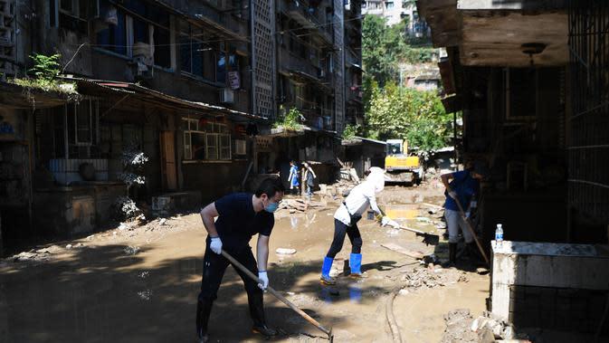 Para sukarelawan membersihkan sebuah jalan di Guojiatuo di Distrik Jiangbei, Chongqing, China barat daya (23/8/2020). Upaya bantuan bencana dilakukan di Chongqing setelah air banjir surut. (Xinhua/Wang Quanchao)
