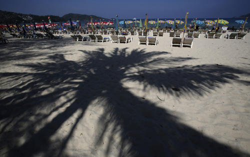 In this March 13, 2014 photo, tourists spend time on Patong Beach in Phuket province, southern Thailand. Thailand's sapphire blue waters, wildlife parks, delicious cuisine and raunchy red light districts have attracted tourists for decades. Phuket is one of Thailand's tourism honeypots. Tourists flock here in droves each year for its sun, sand and laid back ambience. And some lose their passports along the way. (AP Photo/Sakchai Lalit)