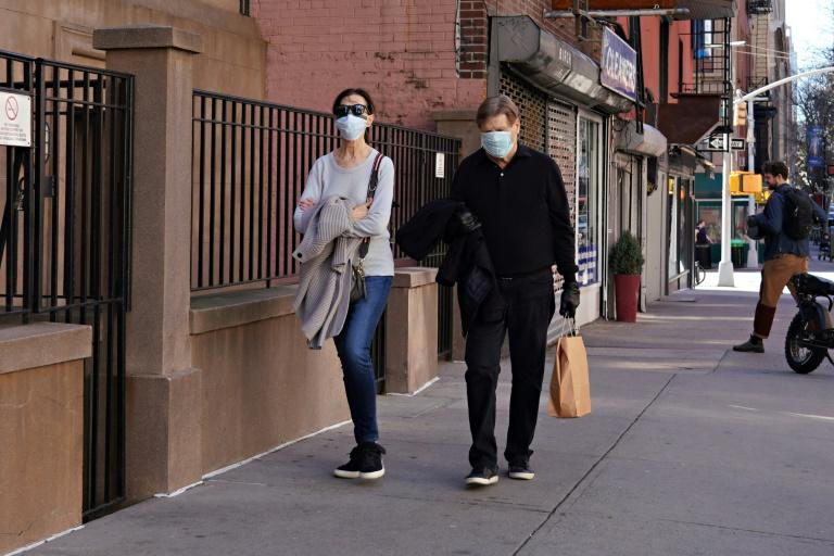 Two people wearing protective masks walk in New York city's Upper East Side neighborhood as the coronavirus continues to spread