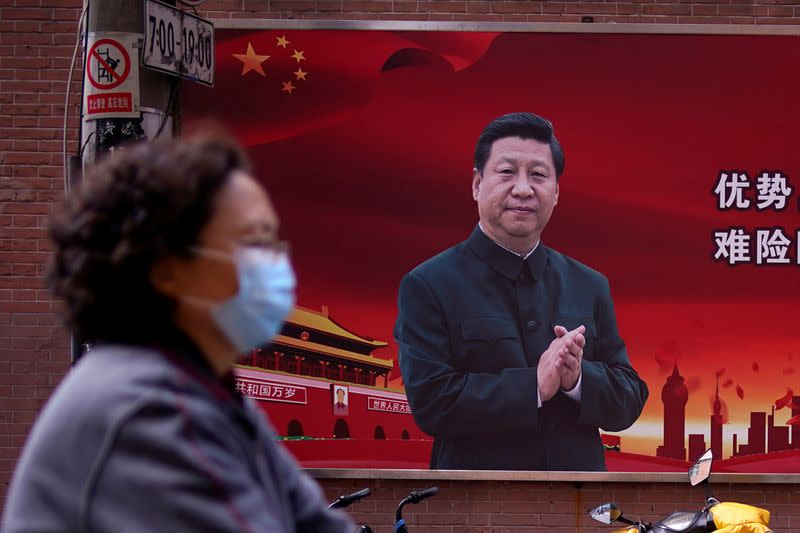 A woman wearing a protective mask is seen past a portrait of Chinese President Xi on a street as the country is hit by an outbreak of the coronavirus, in Shanghai