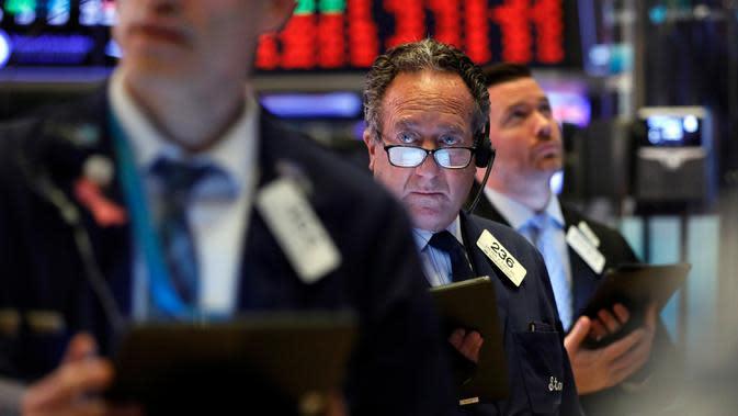 Steven Kaplan (tengah) saat bekerja dengan sesama pialang di New York Stock Exchange, Amerika Serikat, Rabu (11/3/2020). Bursa saham Wall Street anjlok karena investor menunggu langkah agresif pemerintah AS atas kejatuhan ekonomi akibat virus corona COVID-19. (AP Photo/Richard Drew)