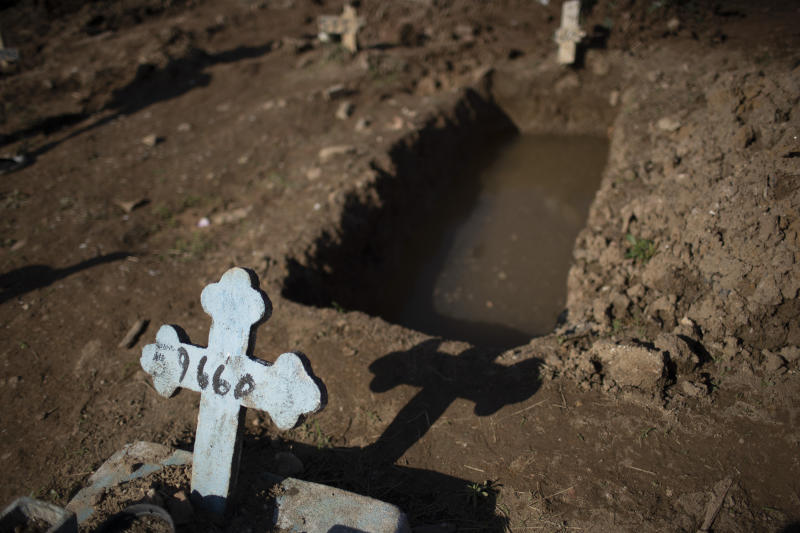 A cross with a number marks an empty grave at the Caju cemetery where many COVID-19 victims are being buried in Rio de Janeiro, Brazil, Wednesday, May 20, 2020. (AP Photo/Silvia Izquierdo)