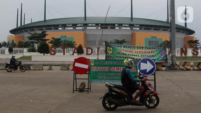 Pengendara motor melintasi jalan depan Stadion Pakansari, Kab Bogor, Jawa Barat, Senin (13/4/2020). Bupati Bogor Ade Yasin menyatakan Pembatasan Sosial Berskala Besar pencegahan penularan virus COVID-19 akan fokus di 11 kecamatan yang masuk kategori zona merah. (Liputan6.com/Helmi Fithriansyah)