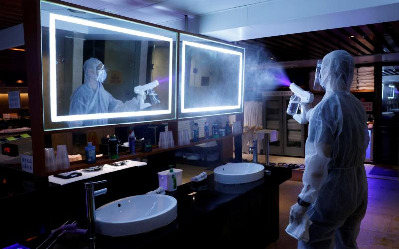 A cleaner wearing a protective suit sprays disinfectant at a sauna and spa centre to prepare the reopening, in Hong Kong - Reuters