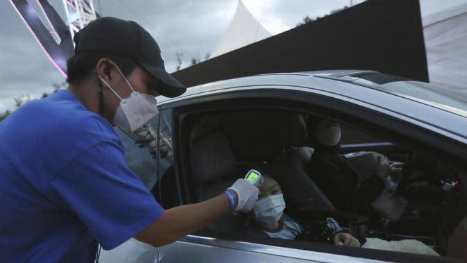 Seorang gadis muda diperiksa suhu tubuhnya saat tiba untuk menyaksikan sirkus drive-in di tempat parkir di Seoul, Korea Selatan, Jumat (25/9/2020). Acara ini digelar untuk memberikan hiburan bagi orang-orang selama wabah virus corona. (AP Photo/Ahn Young-joon)