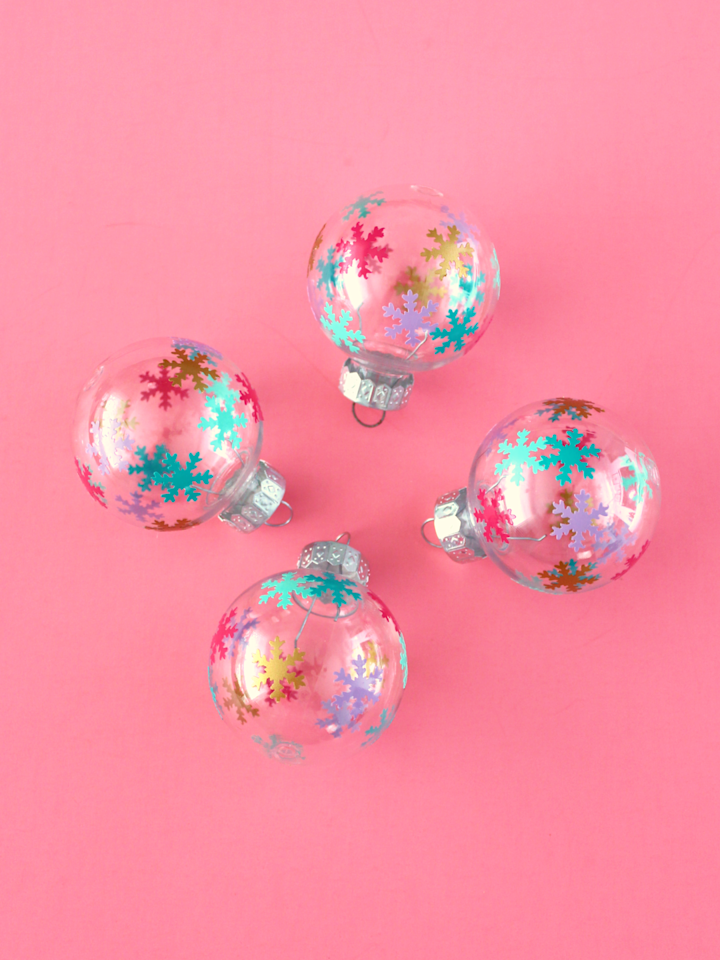 """<p>Dress up ordinary plastic ornaments with colorful vinyl snowflakes. Use a craft punch to create the shapes, and easily transfer them on to the ornaments to add a pop of color to your tree.</p><p><a href=""""https://www.whitehousecrafts.net/post/2018/12/02/mini-diy-colourful-vinyl-snowflake-ornaments"""" target=""""_blank""""><em>Get the tutorial at White House Crafts</em></a></p>"""