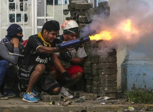 An anti-government demonstrator fires a home-made mortar during clashes with riot police at a barricade in the town of Masaya on June 9, 2018