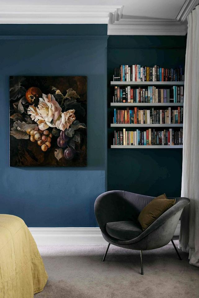 """<p>Create a cozy corner reading nook in your bedroom with a dark paint color, plush fabrics, emotive artwork, and of course, easy-to-reach books. In this bedroom designed by <a href=""""http://arentpyke.com/"""" target=""""_blank"""">Arent & Pyke</a>, the rows of floating shelves provide a home for the occupant's collection. <a href=""""https://www.housebeautiful.com/design-inspiration/house-tours/g1246/colorful-apartment-decorating-ideas/"""" target=""""_blank""""></a></p>"""