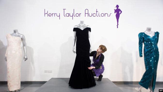 Seorang staf di balai lelang Kerry Taylor Auction di London, 15 Maret 2013, berpose dengan gaun malam Victor Edelstein (tengah) yang digunakan Putri Diana dalam acara jamuan makan malam kenegaraan di Gedung Putih pada 1985. (AFP)