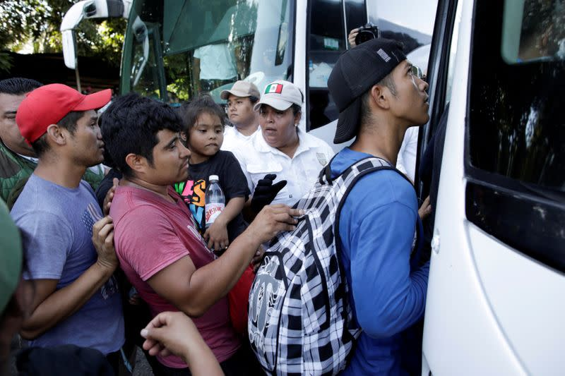 FILE PHOTO: Migration officers guide migrants, mainly from Central America and marching in a caravan, towards a vehicle near Frontera Hidalgo, Chiapas