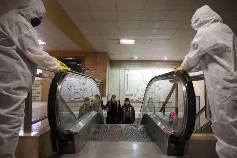 FILE PHOTO: Workers disinfect an escalator in Serdika metro station in Sofia