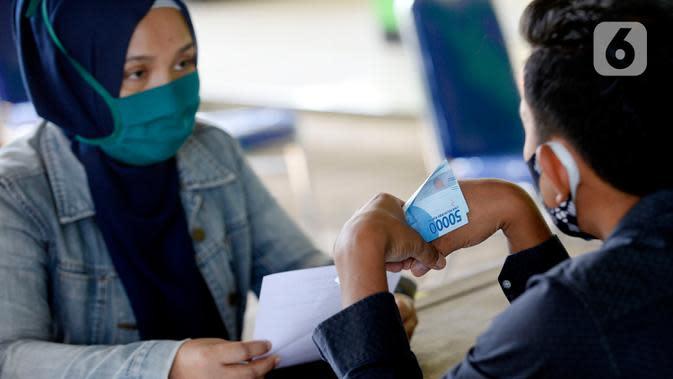 Petugas sedang menyerahkan Bantuan Langsung Tunai Dana Desa (BLT-DD) kepada warga Desa Curug di Kantor Desa Curug, Gunung Sindur, Kabupaten Bogor, Jawa Barat, Kamis (17/09/2020). Bantuan tersebut diberikan kepada 155 per KK untuk bisa mengurangi akibat terdampak COVID-19. (merdeka.com/Dwi Narwoko)