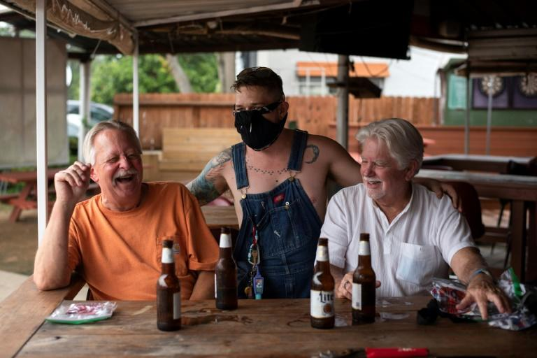 Patrons at the West Alabama Ice House in Houston have beers before Texas Governor Greg Abbott's order that all bars are to be closed amid a surge in coronavirus cases