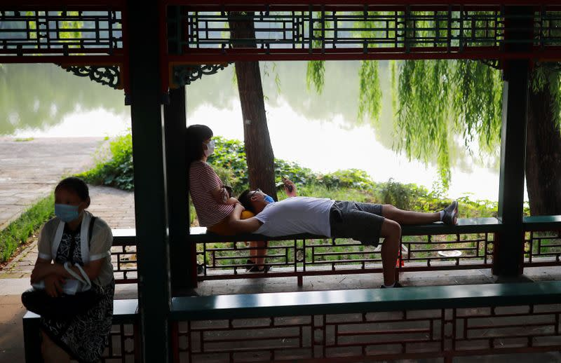 People wearing protective masks relax in the park at Summer Palace on a public holiday, after a new outbreak of the coronavirus disease (COVID-19), in Beijing