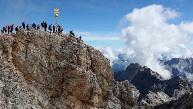 Orang-orang mengantre untuk mencapai puncak salib di puncak gunung tertinggi Jerman, Zugspitze, dekat Garmisch-Partenkirchen, Jerman pada 19 Agustus 2020. Setiap tahunnya gunung dengan ketinggian 2.962 meter tersebut membuat sekitar setengah juta pengunjung terpesona. (AP Photo/Matthias Schrader)