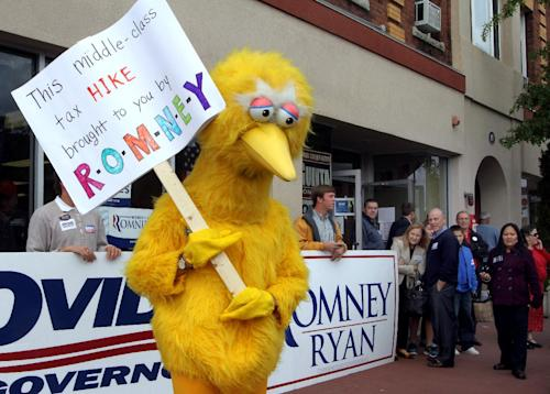 A person dressed up as Big Bird holds a sign against Republican presidential candidate, former Massachusetts Gov. Mitt Romney outside the Romney headquarters, Monday, Oct. 8, 2012 in Derry, N.H. where House Speaker John Boehner of Ohio was about to speak to supporters. (AP Photo/Jim Cole)