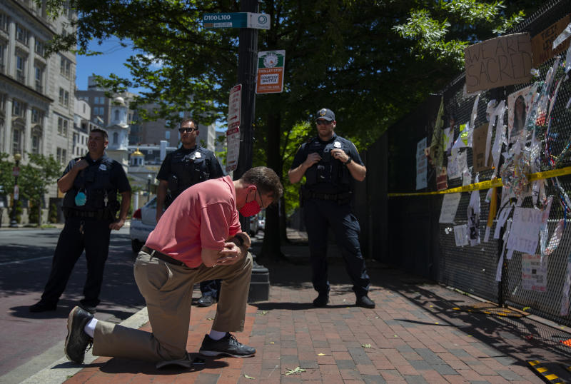 FILE - In this June 24, 2020, file photo members of the Metropolitan Police wait as a man pauses to bow his head on one knee at the parameter fence along H Street NW and Lafayette Square Park near the White House in Washington as they clear the area of pedestrians. As a national reckoning over racism and policing grips the nation, white Democrats are far more likely now than they were a few years ago to think police brutality is a serious issue — a dramatic shift in public opinion that some say could shape the November presidential election. (AP Photo/Carolyn Kaster, File)