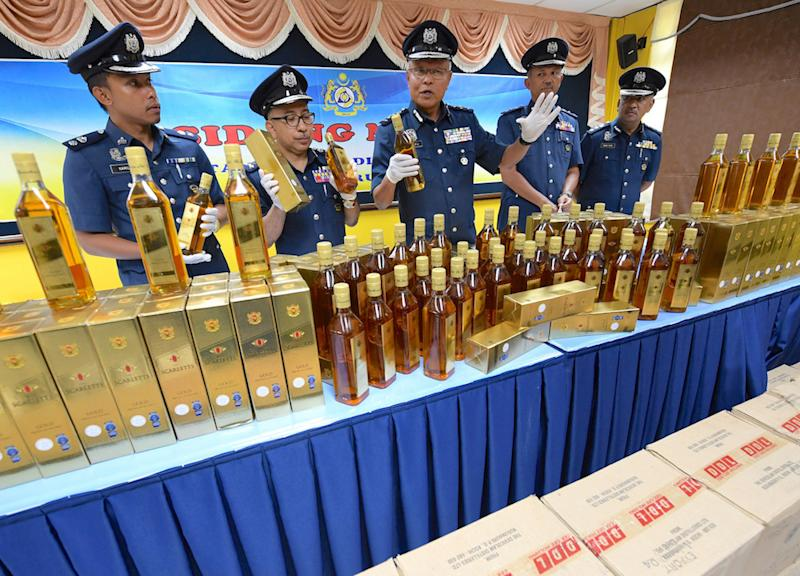 Customs deputy director (Enforcement and Compliance) Datuk Seri Zulkifli Yahya poses for pictures with the seized alcohol during a press conference in Alor Setar October 4, 2018. — Bernama pic