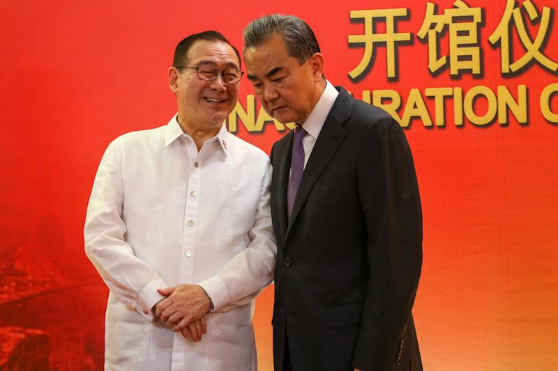FILE PHOTO: Philippines' Secretary of Foreign Affairs Teodoro Locsin Jr. (L) talks to Chinese Foreign Minister Wang Yi during the inauguration of the Consulate General of China in Davao, in the southern island of Mindanao on October 28, 2018. (Photo: MANMAN DEJETO/AFP via Getty Images)