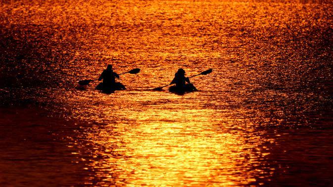 Orang-orang menyaksikan matahari terbenam sambil berperahu di Shawnee Mission Lake, Shawnee, Kansas, Amerika Serikat, Jumat (9/10/2020). Matahari terbenam terus lebih cerah dari biasanya karena asap dari kebakaran hutan barat terus melayang di seluruh negeri. (AP Photo/Charlie Riedel)
