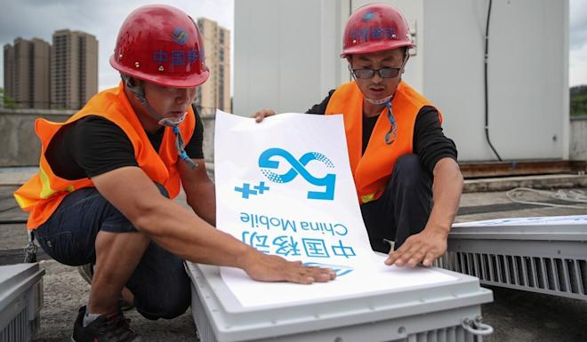 Workers place a China Mobile 5G sign on equipment as they set up a 5G network base station in Fenggang, Guizhou province, China on May 26. Photo: cnsphoto via Reuters