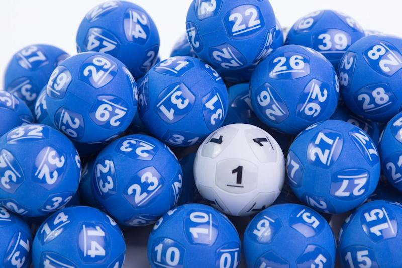 A white powerball lotto ball is nestled among blue lotto balls.