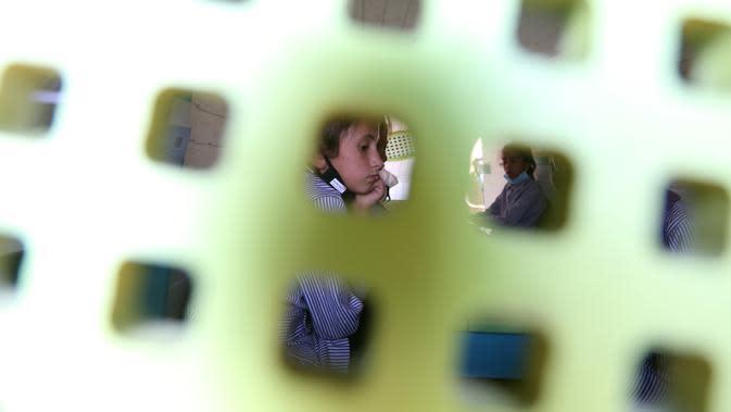 Seorang siswa Palestina duduk dalam bus yang telah dialihfungsikan menjadi ruang kelas keliling di Khirbet Ibziq, dekat Kota Tubas, Tepi Barat, 8 Oktober 2020. Sebuah asosiasi lokal mengalihfungsikan sebuah bus menjadi perpustakaan dan ruang kelas keliling. (Xinhua/Ayman Nobani)