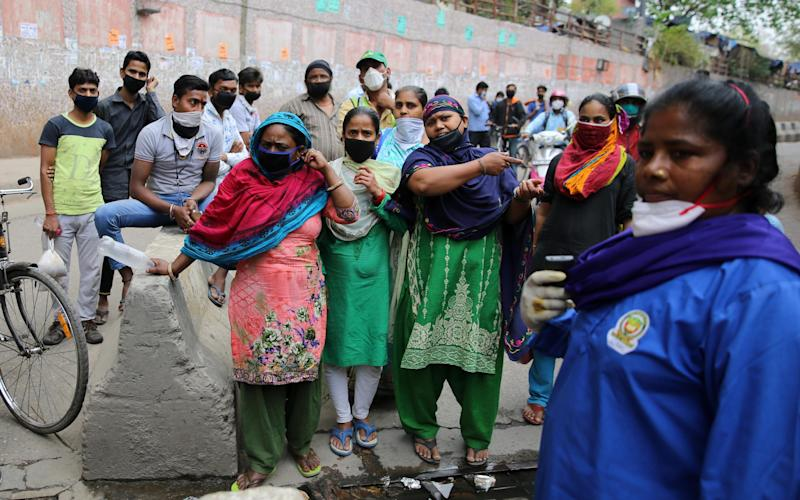 Women stranded in Nizamuddin plead to be let through a makeshift barricade to their homes in Sarai Kale Khan - Cheena Kapoor