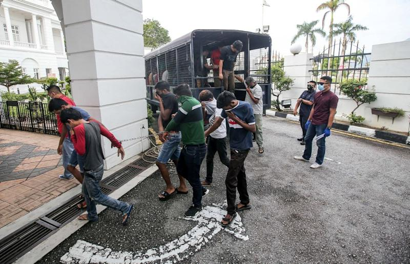 Police round up detainees who flouted the movement control order at the Ipoh Magistrate's Court April 2, 2020. — Picture by Farhan Najib